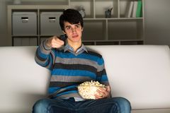 Young man watching television with popcorn Stock Photography