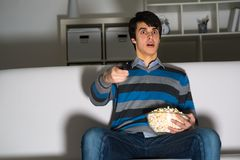 Young man watching television with popcorn Royalty Free Stock Images