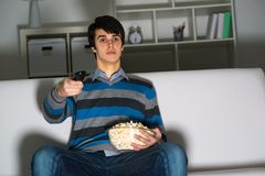 Young man watching television with popcorn Stock Images