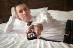 Young man watching TV. Young businessman wearing white shirt and necktie lying on the bed in the hotel room with remote control in his hand, preparing to watch Stock Photo