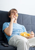 Young man watching tv and eating chips Stock Images