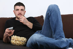 Young man watching tv and eating popcorn. Young man lying on a sofa, watching tv and eating popcorn Stock Image
