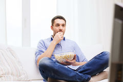 Young man watching tv and eating popcorn at home. Sports, food, happiness and people concept - young man watching tv and eating popcorn at home Royalty Free Stock Photo