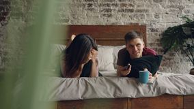 Young man is watching TV with his girlfriend lying on bed and holding remote, they are holding pillows and mug. Young man is watching TV with his attractive stock footage