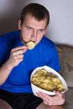 Young man watching tv at home and eating chips Royalty Free Stock Images