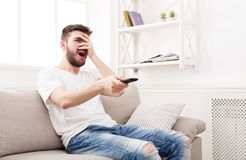 Thrilled young man watching tv at home. Young man watching tv at home. Thrilled guy pointing with remote controller on tv-set, copy space Royalty Free Stock Image