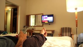 Young man watching tv in hotels room. Young man using tv in hotels room, feet in hotel stock video