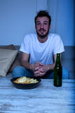 Young man watching TV at nighttime with chips and beer Royalty Free Stock Images