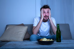 Young man watching TV at nighttime with chips and beer Stock Photo