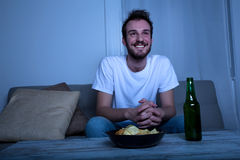 Young man watching TV at nighttime Stock Images