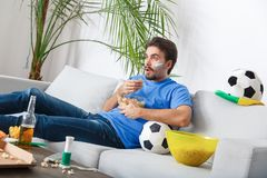 Young man sport fan watching match in a blue t-shirt eating chips royalty free stock photos