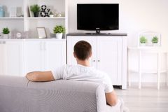 Young man watching TV on sofa. At home Stock Images