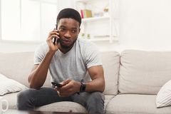 Young man watching tv and talking on mobile in living room. Young serious african-american man watching tv and talking on smartphone pointing with remote Royalty Free Stock Image