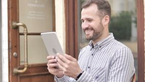 Young Man Watching Video on Tablet while Sitting Outdoor. 4k high quality, 4k high quality stock footage