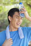 Young Man with Water Bottle after Exercising in Park Stock Image