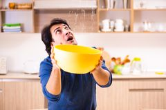 The young man in water leakage from the neighbors concept. Young man in water leakage from the neighbors concept stock photo