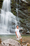 Young man and waterfall Stock Image