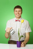Young man watering a flower Stock Images