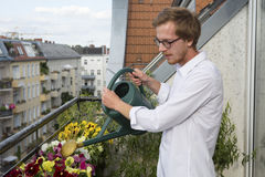 Young man watering plants on balcony Royalty Free Stock Images