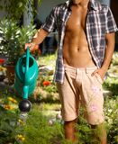 Young man watering plants at summer Stock Images