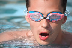 Young man in watersport goggles swimming in pool Royalty Free Stock Images