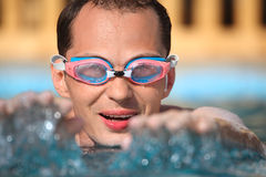 Young man in watersport goggles swimming in pool Stock Image