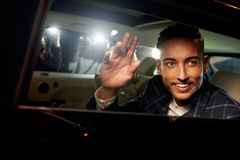 Young man waving from the back of a chauffeur driven limo Stock Photos