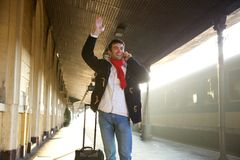 Young man waving hand at train station stock photo