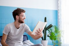 Young man wear glasses reading book on sofa with enjoy and laugh in the living room Royalty Free Stock Photography
