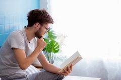 Young man wear glasses reading book on sofa in the living room Stock Photography