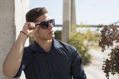 Young man wear sunglasses lean on a colum. Young man wear and hold the sunglasses lean on a column, shoot take place outdoor. Looking away Stock Image