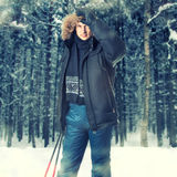 Young man wearing black fur hood winter jacket. Young man skier wearing black fur hood winter jacket and holding sticks in winter forest Royalty Free Stock Images