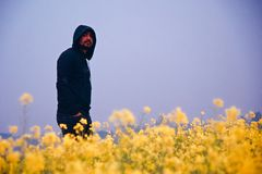 Young man wearing hood dress standing around an agricultural field royalty free stock photo