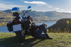Young man wearing a black leather jacket and jeans sits outdoor. On a ground at a motorcycle, resting on a mountain above the river. Lifestyle, travel. Copy stock image