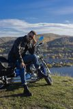 Young man wearing a black leather jacket, sunglasses and jeans s. Its outdoor on a motorcycle, resting on a mountain above the river. Lifestyle, travel. Copy stock images