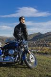 Young man wearing a black leather jacket, sunglasses and jeans s. Tays outdoor at a motorcycle, resting on a mountain above the river. Lifestyle, travel. Copy royalty free stock image