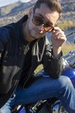 Young man wearing a black leather jacket, sunglasses and jeans s. Its outdoor on a motorcycle, resting on a mountain above the river. Lifestyle, travel. Copy stock photo