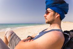 Young man wearing blue turban sitting sand beach. Young guy man sitting resting Mediterranean Sea sand beach, wearing blue Tuareg turban cheche, looking at royalty free stock image