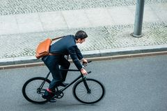 Young man wearing business suit while riding an utility bicycle. High angle view of young man wearing business suit while riding an utility bicycle on the street royalty free stock photos