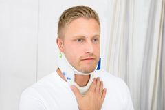 Young man wearing cervical collar. Man Suffering From Neck Ache Using Cervical Collar stock image
