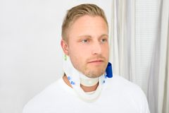 Young man wearing cervical collar. Man Suffering From Neck Ache Using Cervical Collar royalty free stock photos