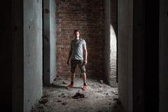 Young man wearing a check shirt and shorts against a brick wall. Horizontally framed shot stock photography