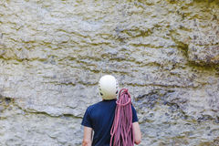 Young man wearing in climbing equipment with rope standing in front of a stone rock Stock Photos