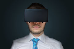 Young man is wearing 3D virtual reality glasses. Low key photo Stock Photography