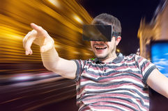 Young man is wearing 3D virtual reality headset and is playing video games. Stock Image