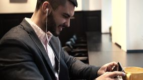 Young man wearing dark suit using smartphone in coffee shop. Young caucasian or middle eastern man using his smartphone in coffee shop. Male adult wearing dark stock video