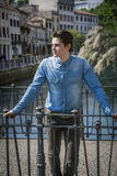 Young man wearing denim shirt on city bridge in Treviso, Italy. Young man leaning on handrail, wearing denim shirt on city bridge in Treviso, Italy stock photo