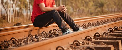 Man sitting on the railway tracks in the afternoon. A young man wearing fashionable dress sitting on a railway tracks in the afternoon stock photography