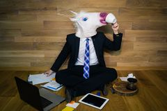 Young man wearing funny mask sits on the floor against a wall and drinks coffee. Unicorn dress a suit and tie and working with documents using laptop and Royalty Free Stock Photos