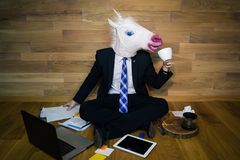 Young man wearing funny mask sits on the floor against a wall and drinks coffee. Unicorn in a suit and tie works in home office on laptop and gadgets on wooden Stock Photos